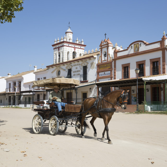 """""""Horse and carriage riding along sand streets with brotherhood houses behind,..."""" stock image"""