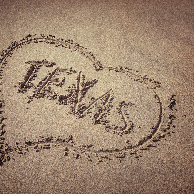 """Texas and heart written on beach sand"" stock image"