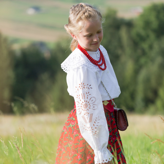 """""""Young girl in traditioal Polish mountain dress stands on green m"""" stock image"""