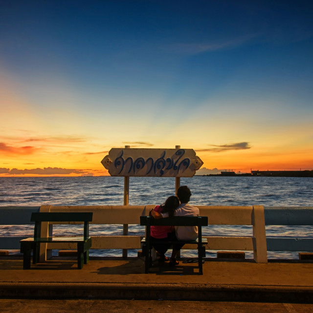 """Couple watching sea sunset with twilight sky"" stock image"