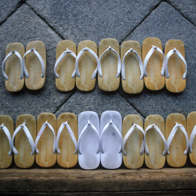 """""""Several pairs of slippers placed on a wooden table, Japan, Asia."""" stock image"""