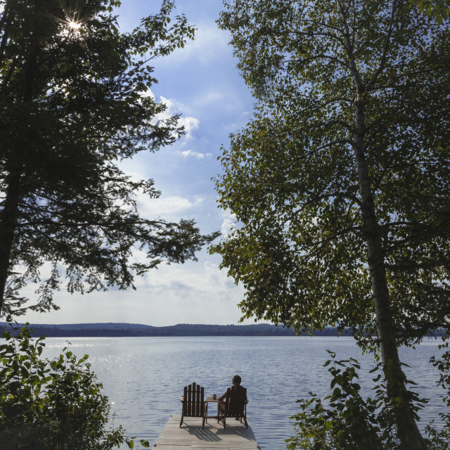 """""""A 45 year-old woman sitting in an adirondack chair on a dock on Spencer Pond..."""" stock image"""