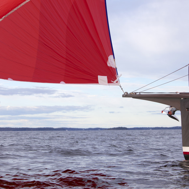 """""""The red spinnaker billows as a luxury sailing yacht cruises along the coast..."""" stock image"""