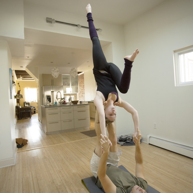 """""""Young couple in a clean apartment practicing acro yoga"""" stock image"""