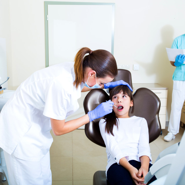 """Young girl getting her dental checkup"" stock image"