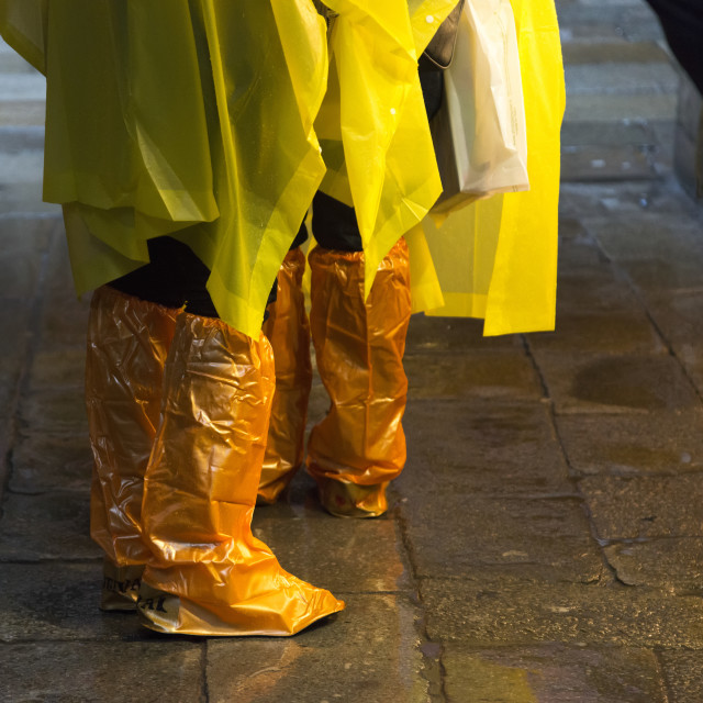 """People Standing With Yellow Rain Ponchos And Footwear Covered In Orange..."" stock image"
