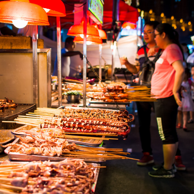 """""""NANNING, CHINA - JUNE 9, 2017: Food on the Zhongshan Snack Street, a food market in Nanning with many people bying food and walking around"""" stock image"""