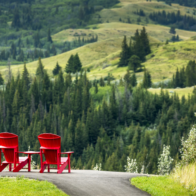 """""""Two Red Adirondack Chairs On A Paved Pathway On Top Of A Hillside Overlooking..."""" stock image"""