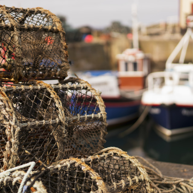"""""""Traps Sitting On The Shore With Fishing Boats Moored In The Background; St...."""" stock image"""
