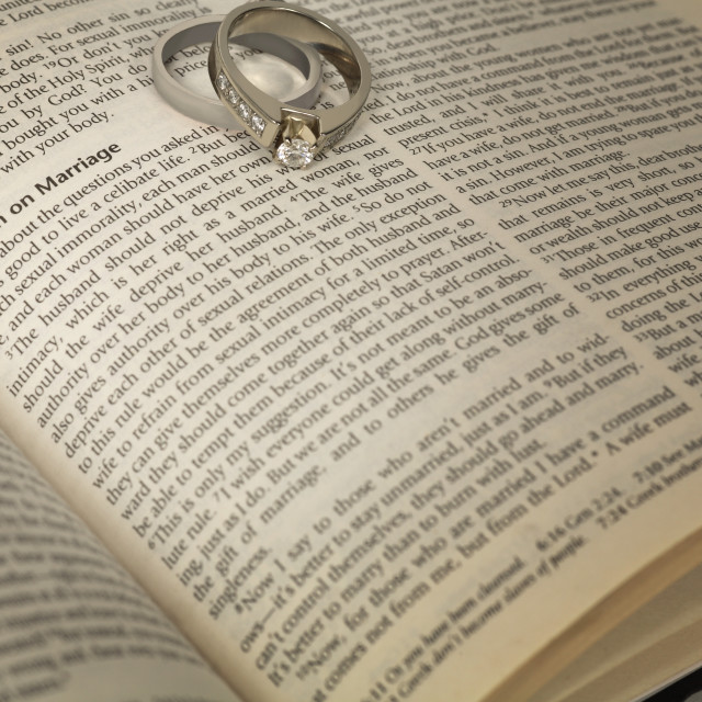 """Wedding Rings On An Open Bible"" stock image"