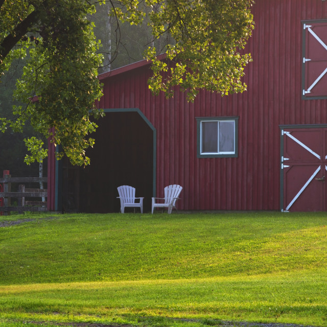 """""""A Red Barn With Two Adirondack Chairs In Front; Iron Hill, Quebec, Canada"""" stock image"""