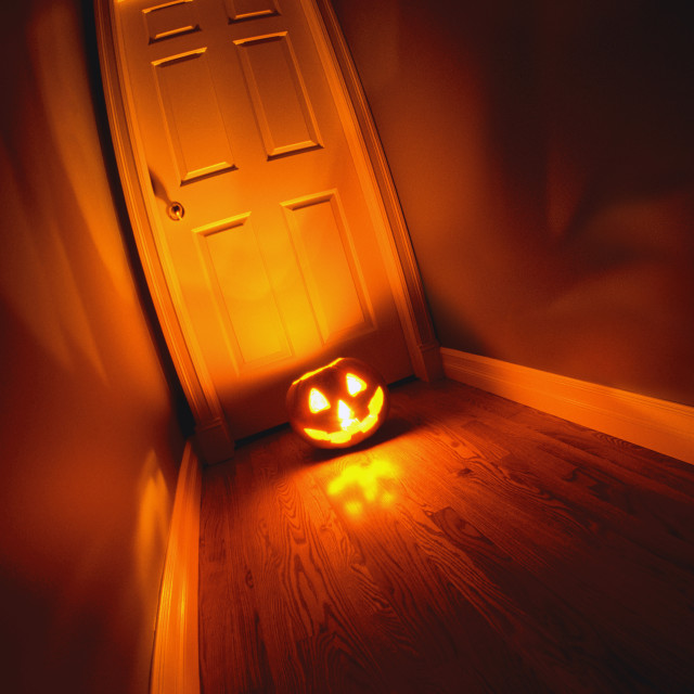 """Lighted Jack-O-Lantern On Floor In Front Of Door"" stock image"