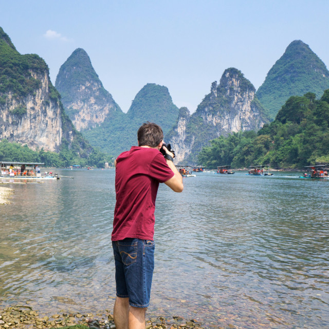"""Man photographing scenery of the Li river in Yangshuo China"" stock image"