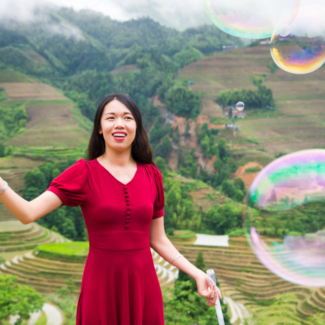 """""""Girl making soap bubbles at rice terrace viewpoint"""" stock image"""