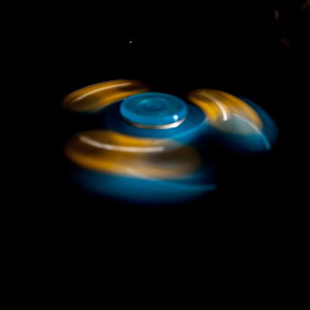 """""""Moving Fidget Spinner on Black"""" stock image"""