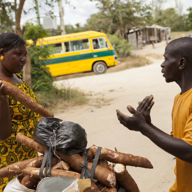 """""""A woman negotiates the price whilst buying yams from a man selling them from..."""" stock image"""