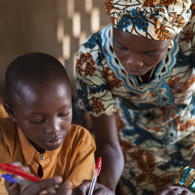 """A teacher helping a young student at a school on Ghana"" stock image"