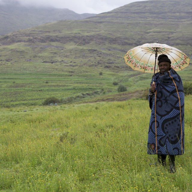 """""""A man holding an umbrella and wrapped in a blue blanket stands in the..."""" stock image"""