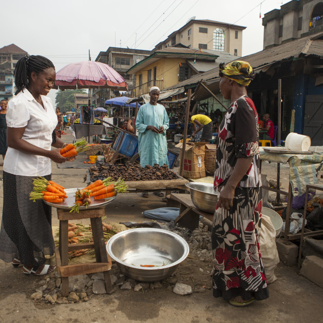 """""""A woman buying carrots in the market in Nigeria."""" stock image"""