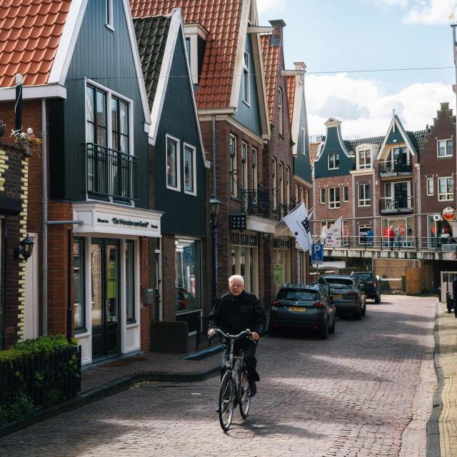 """Resident of the village of Volendam by bike in front of the typical traditional houses, Netherlands."" stock image"