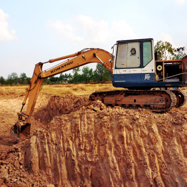 """An excavator digs a pond"" stock image"