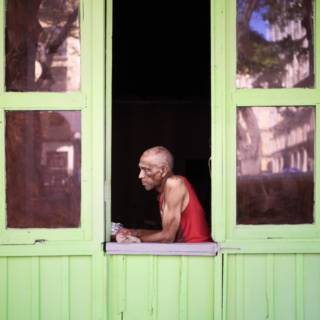 """Man sits in doorway window in Havana Cuba"" stock image"