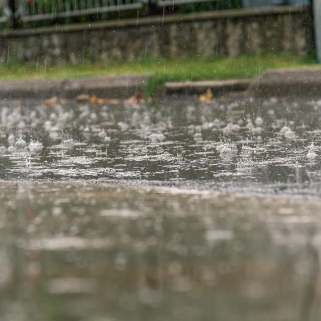 """heavy rain drops falling on city asphalt during downpour"" stock image"