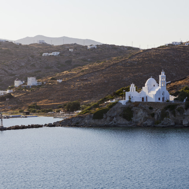 """Port And White Church On A Cliff At The Water's Edge; Ios, Greece"" stock image"