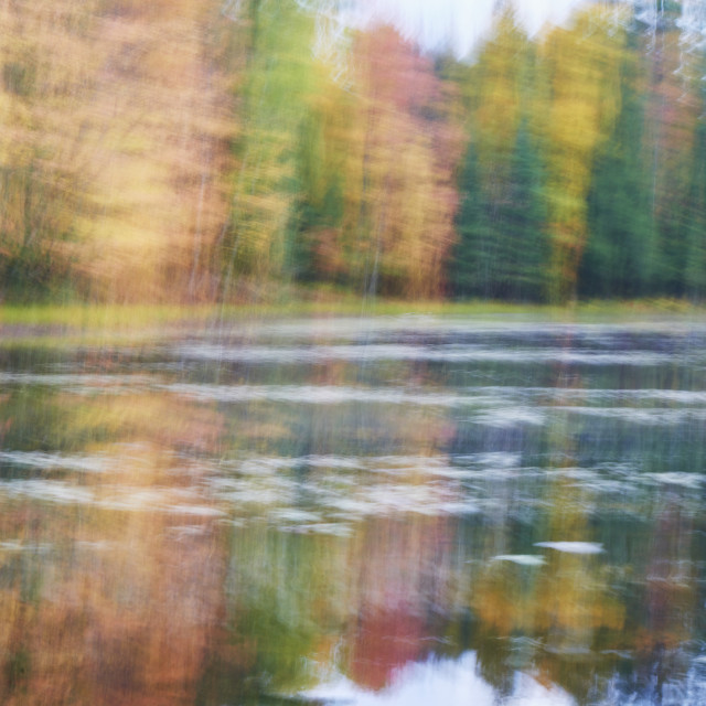 """Blurred Autumn Coloured Trees Along The Shoreline Reflected In A Tranquil..."" stock image"