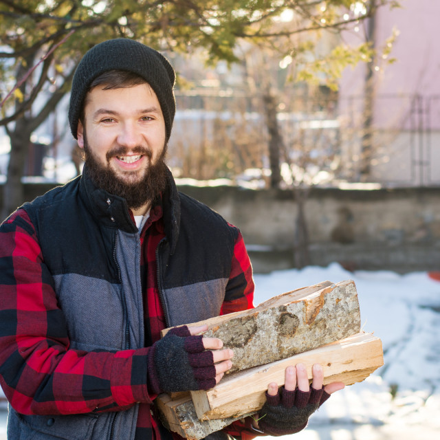 """""""Masculine man carrying firewood"""" stock image"""