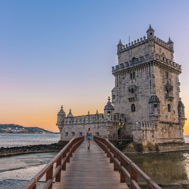 """Girl walks along Belém Tower in Lisbon, Portugal"" stock image"