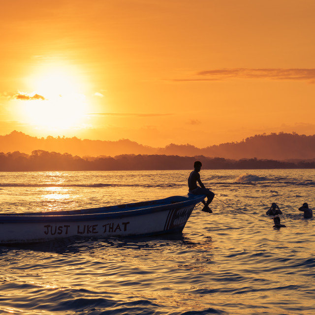 """Puerto Viejo de Talamanca, Costa Rica - March 22, 2014: People swimming at the beach in Puerto Viejo de Talamanca, Costa Rica, at sunset"" stock image"