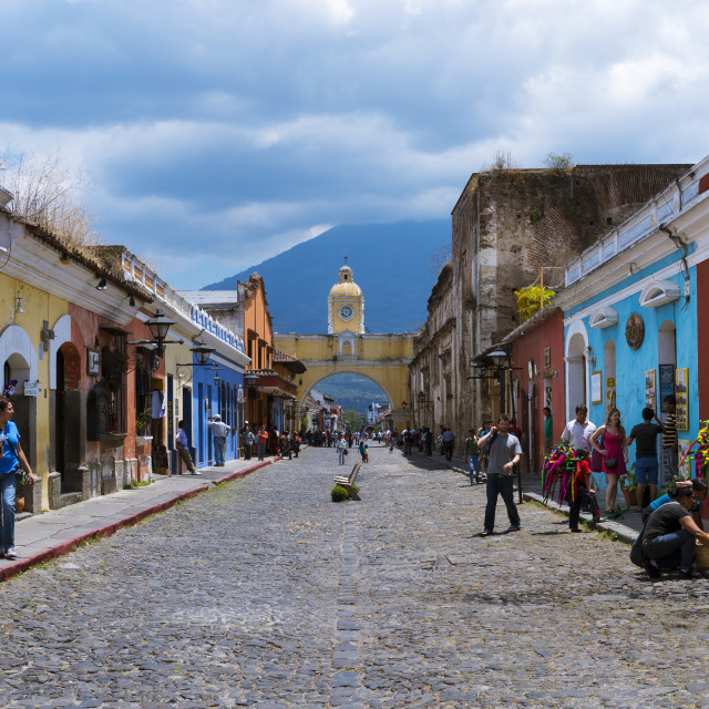 """Antigua, Guatemala - April 16, 2014: View of a cobblestone street in the old city of Antigua with the Agua Volcano on the background, in Guatemala"" stock image"