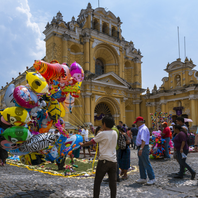 """Antigua, Guatemala - April 17, 2014: Young boy selling baloons in a street of the old city of Antigua with the San Pedro Hospital on the background, in Guatemala"" stock image"
