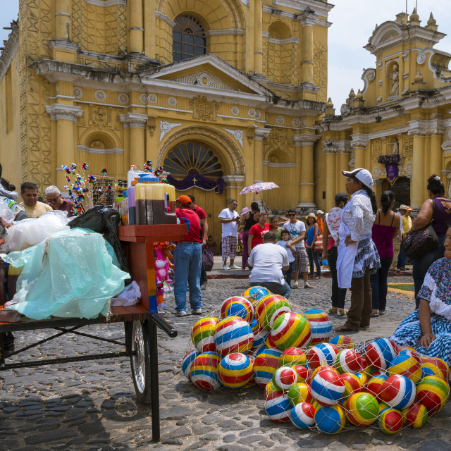 """Antigua, Guatemala - April 17, 2014: Woman selling selling colorful rubber balls in a street of the old city of Antigua with the San Pedro Hospital on the background, in Guatemala"" stock image"