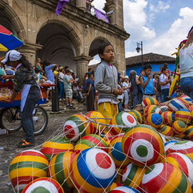 """Antigua, Guatemala - April 18, 2014: Young girl selling colorful rubber balls in a street of the old city of Antigua, in Guatemala"" stock image"