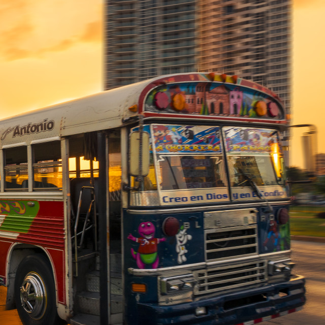 """Panama City, Panama - March 18, 2014: A Red Devil bus in Panama City with modern building on the background at sunset, in Panama."" stock image"