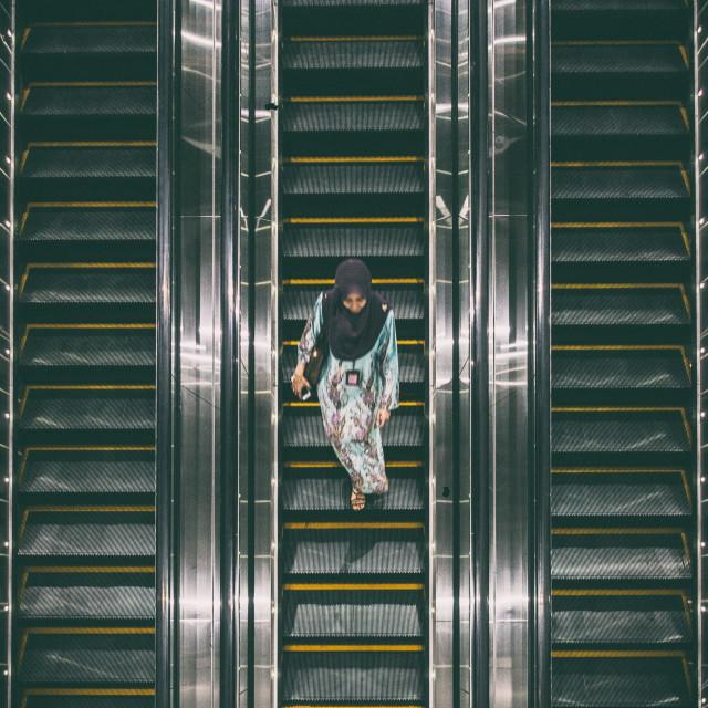 """Muslim woman on an escalator"" stock image"