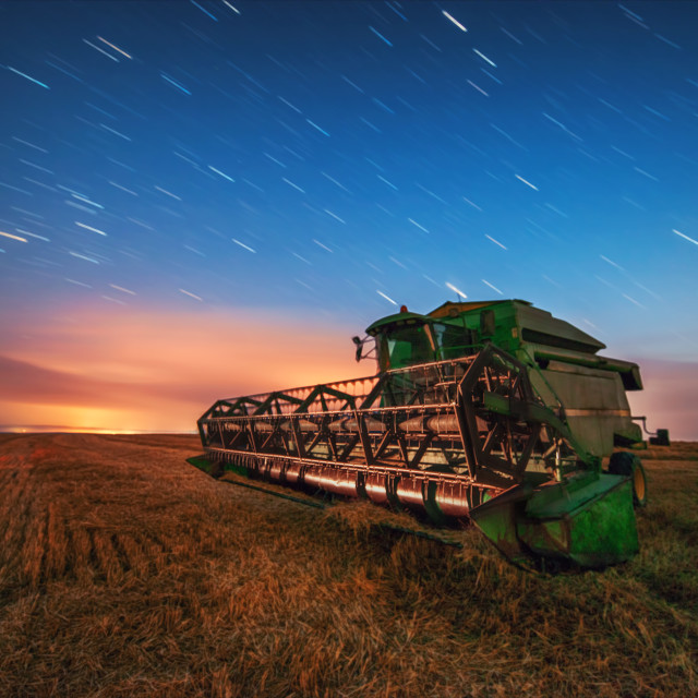 """Combine harvester machine working in a wheat field, sunset and s"" stock image"