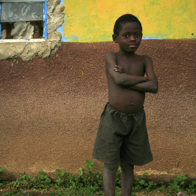 """little African boy with no shirt on in front of colourful clay house in..."" stock image"