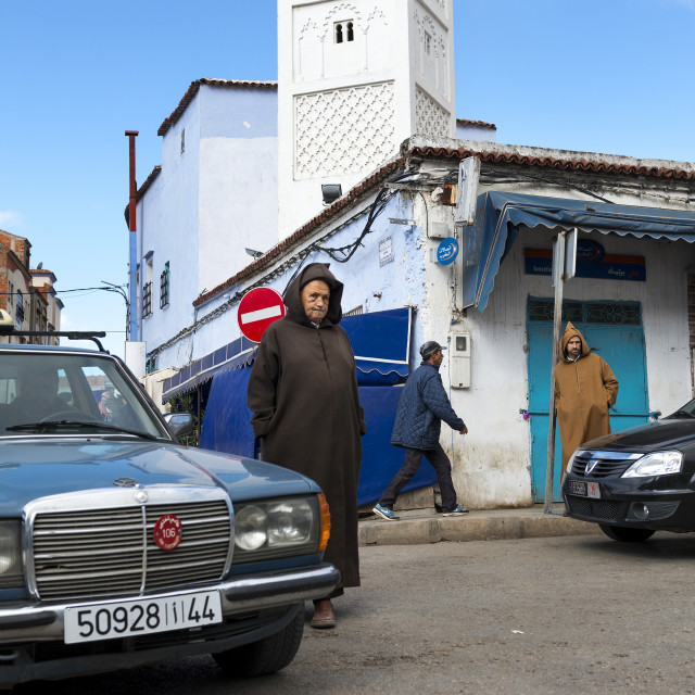 """Chefchaouen, Morocco - April 10, 2016: People in a street with cars and shops in the town of Chefchaouen in Morocco, North Africa"" stock image"