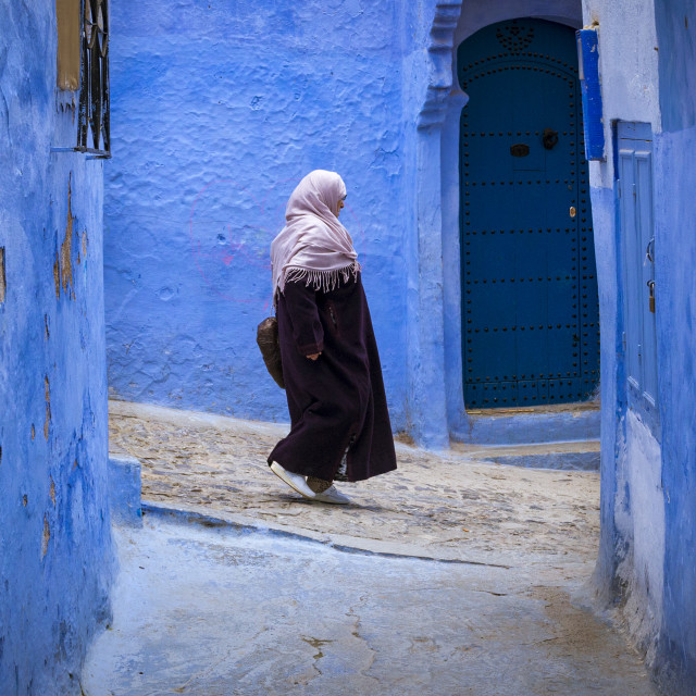 """Chefchaouen, Morocco - April 10, 2016: Moroccan woman walking in a narrow street in the town of Chefchaouen in Morocco, North Africa"" stock image"