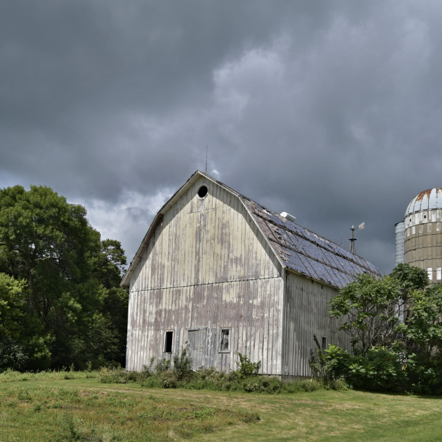 """Weathered Barn and Silo under a cloudy sky"" stock image"