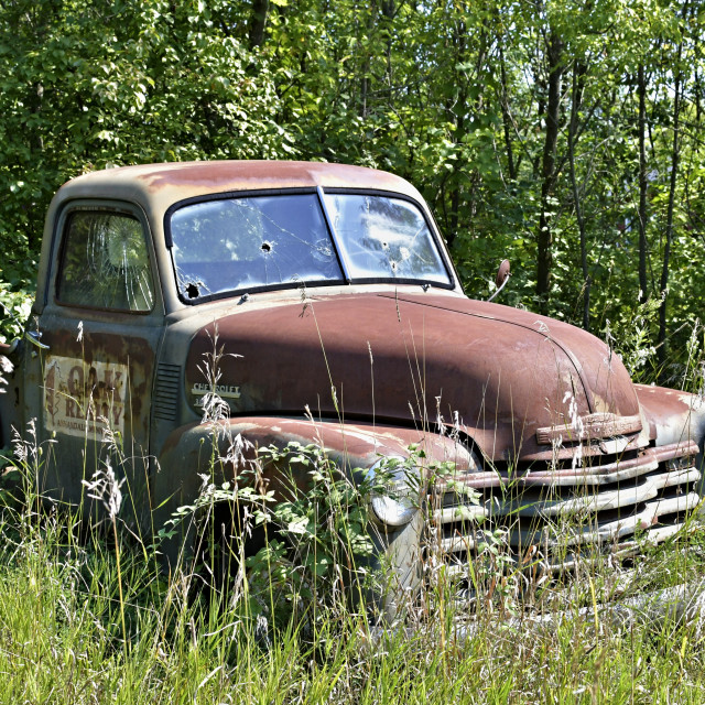 """Old Cheverolet pickup truck sitting in a field"" stock image"