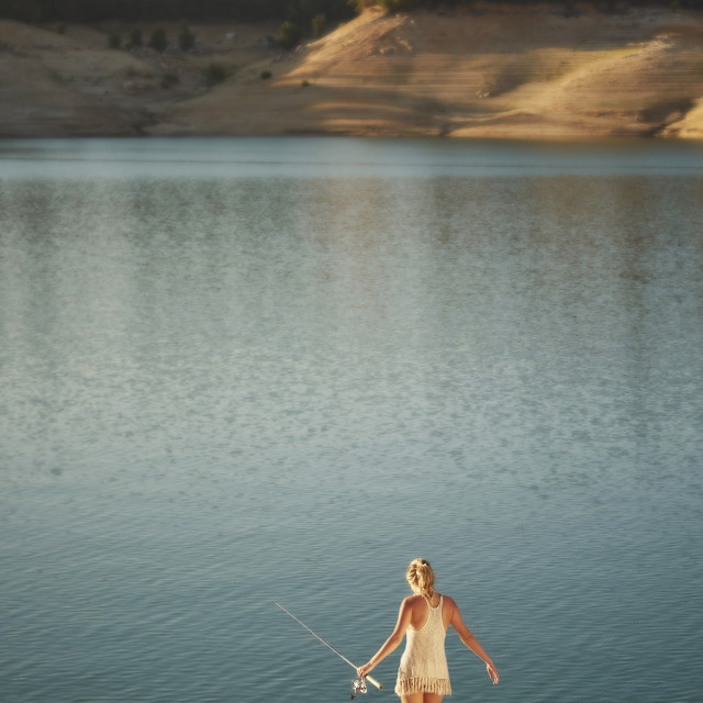 """Young Woman Walkin To a Lake With a Fishing Pole"" stock image"
