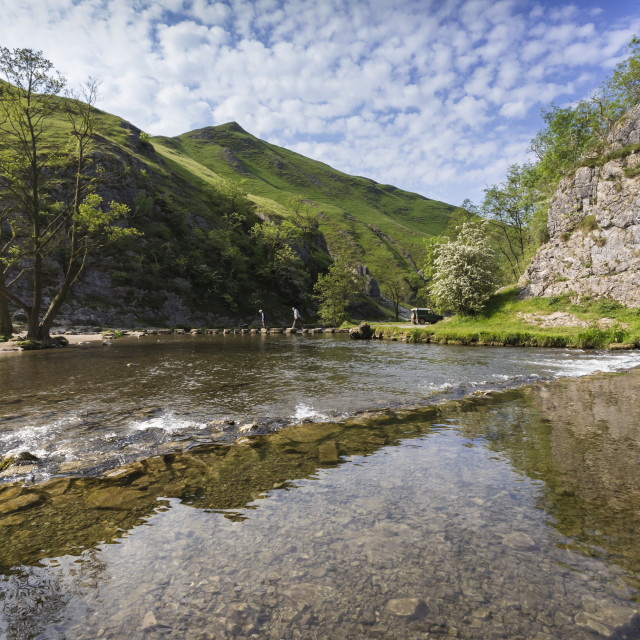 """Dovedale reflections, hikers on stepping stones and Thorpe Cloud, limestone..."" stock image"