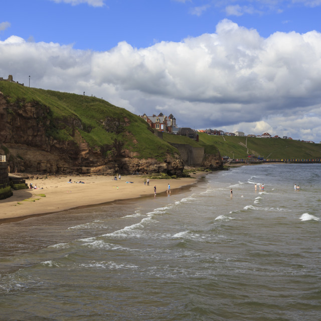 """""""Bathers on West Cliff Beach, backed by grassy cliffs in summer, Whitby, North..."""" stock image"""