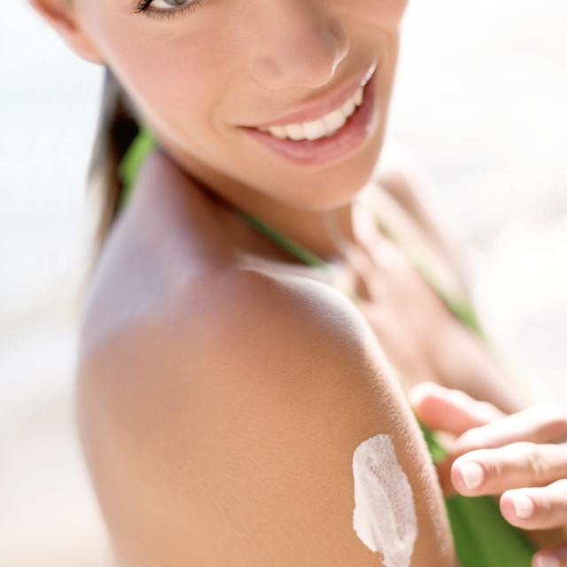 """Woman applying sunscreen"" stock image"