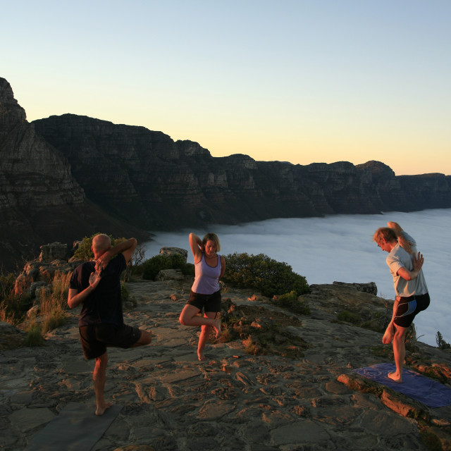"""yoga on top of Lions Head at sunrise with Table Mountain and the Twelve..."" stock image"