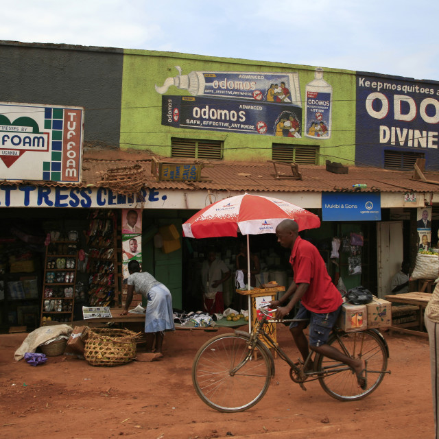 """""""African man rides a bicycle past small shops, UgandaNovember 23, 2010{iptc..."""" stock image"""